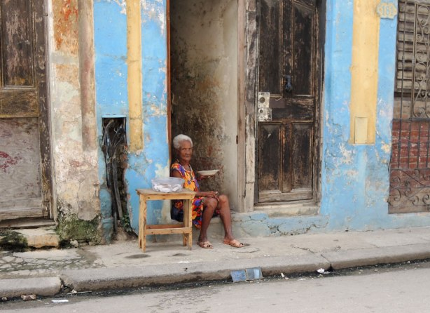 picture taken inthe old part of the city of Havana Cuba - a woman is sitting in a doorway with a small table beside her and a bowl in her hand.  She appears to be scowling at the camera