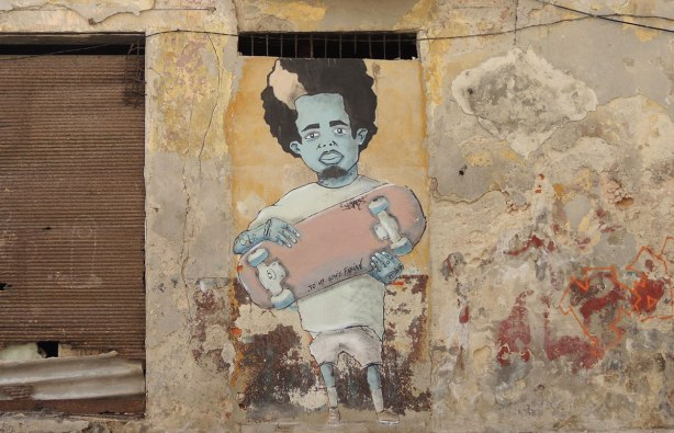 picture taken inthe old part of the city of Havana Cuba - graffiti on a wall.  A man with curly black hair and a blue face is holding a skateboard.
