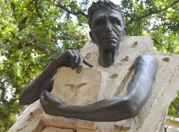 picture taken in the old part of the city of Havana Cuba - the upper part of a statue in a park, a man's head and arms are poking out of a square rock like structure