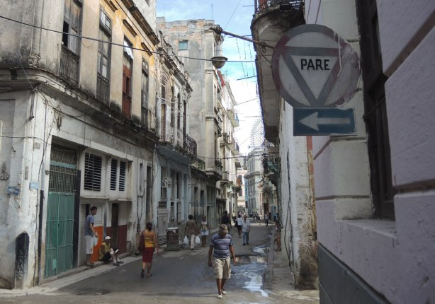 picture taken in the old part of the city of Havana Cuba - street scene.  People walking in a narrow street with buildings close to the edge of the street on both sides.