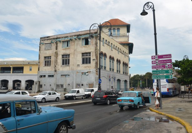 picture taken in the old part of the city of Havana Cuba - a main street, cars on the road, an old building, and some modern colour coded traffic signs in purple and green.