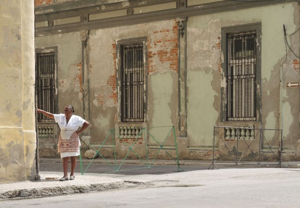 picture taken inthe old part of the city of Havana Cuba - a woman in a white blouse and white skirt and multicoloured apron leans agains the corner of the exterior of a building.  A weathered old building is behind her.