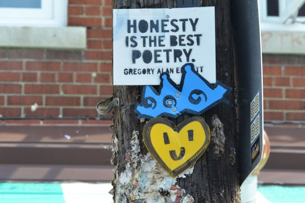 a yellow happy face lovey heart on a telephone pole, with a blue crown on top of it as well as a stencilled sign that reads Honesty of the best poetry, Gregory Alan Elliott