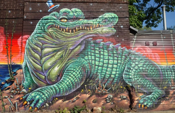Intricate street art painting of a crocodile or alligator on a wall in an alley. Alley animal.