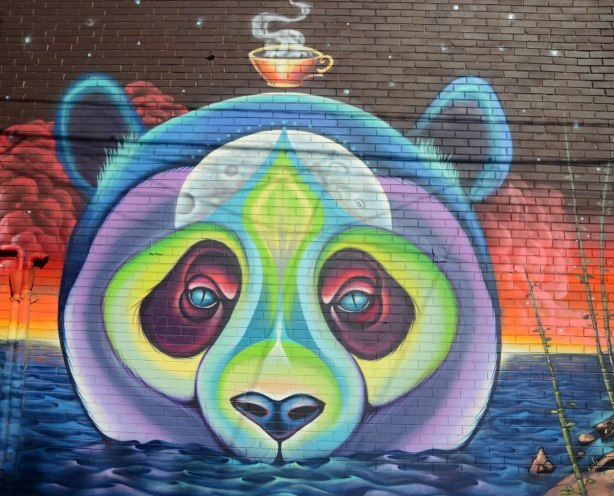 The face of a bear, perhaps panda bear, but in purples and greens. It is in water up to its nose. A steaming tea cup floats above its head.