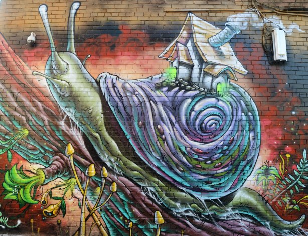 large street art painting of a snail with a tiny house on the back of its shell. The piece is signed by Smoky