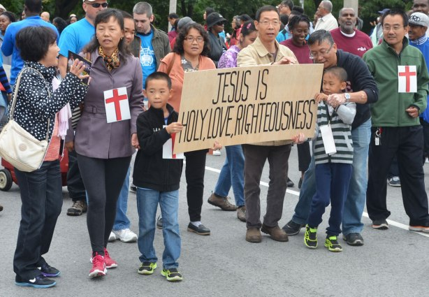 Two boys are holding a brown banner that says Jesus is holy, love, rightousness. A group of Asian people are walking with them in a parade.