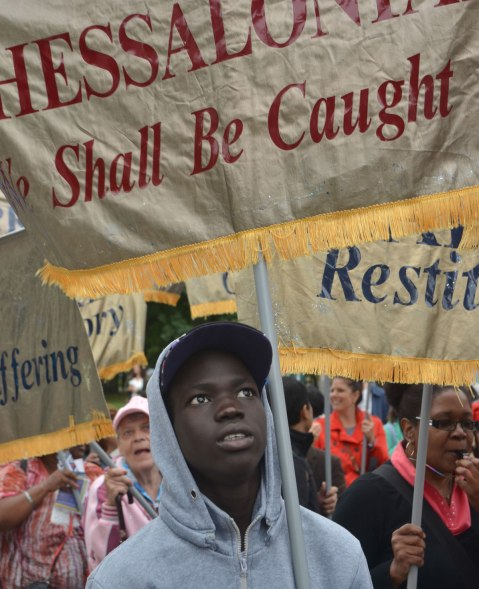 A young black man is holding a banner in a parade. He is looking upwards. Other people around him are also holding banners. The banners are gold and each one has the name of a book of the bible on it.