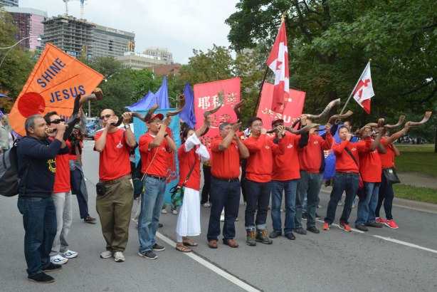 A group dressed in red t-shirts blowing horns