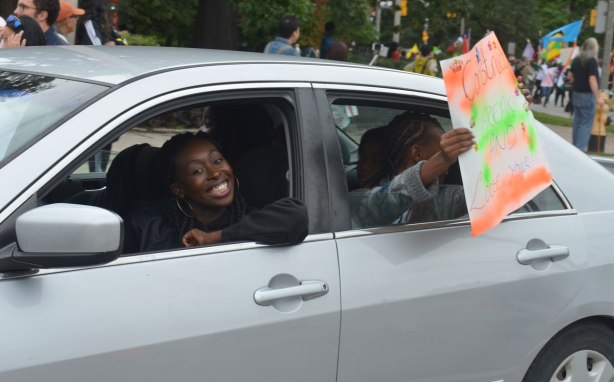 Two women in a car. The driver is making a smiley face. The women in the backseat is holding a sign out the window that says