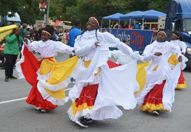 Four women wearing long ruffled skirts in white, red and yellow, swishing their skirts side to side as they walk in a parade