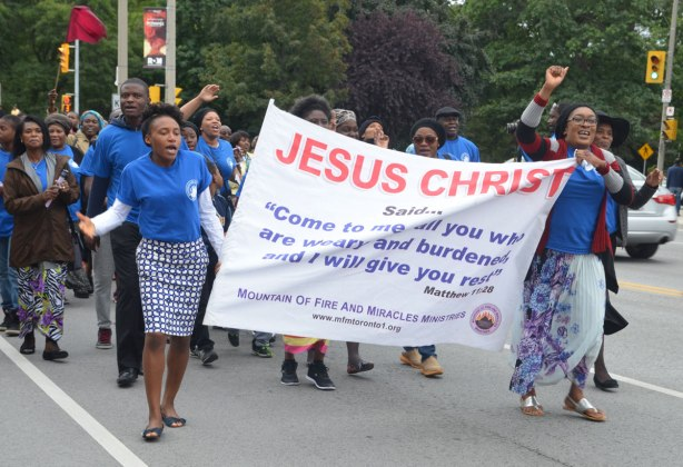 Two women in blue t-shirts are holding a banner in a parade. Others are walking with them. The banner says Jesus Christ in large red letters. There are smaller words in blue below that are a verse from Matthew that starts with Come to me all you who are weary and burdened and I will give you rest. The group is from the Mountain of Fire and Miracles Ministry