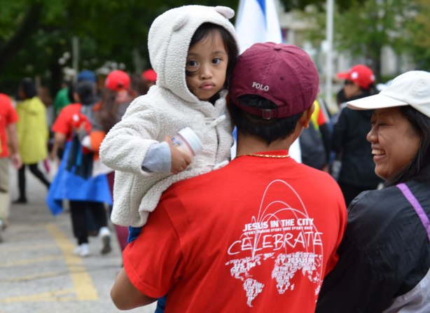 A man wearing a t-shirt that says Jesus in the City Celebration on the back. He is holding a young girl who is wearing a jacket with a hood that has little ears on it.