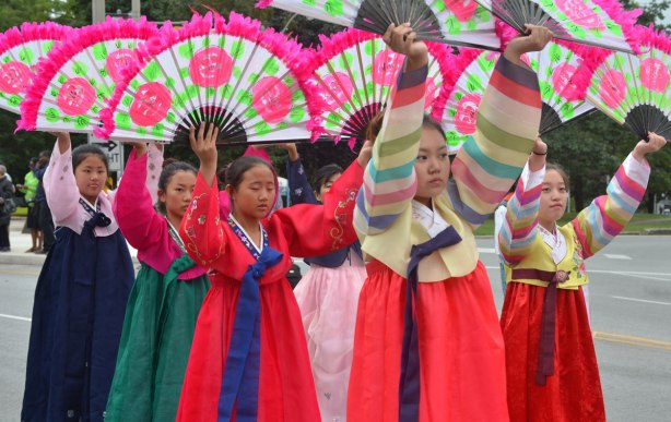 A line of Japanese women in kimonos are carrying large open fans above the heads. The fans have big pink flowers on them as well as a pink feathery border.