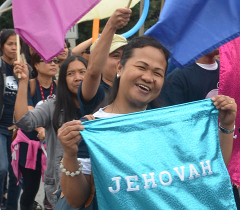 A woman is holding a shiny turquoise fabric sign with the word jehovah on it.