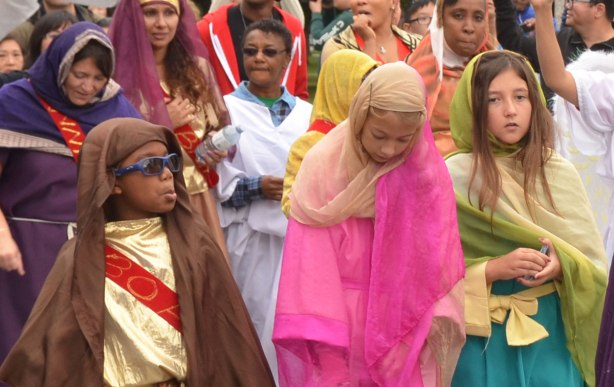Kids dressed up in colourful costumes and walking in a parade