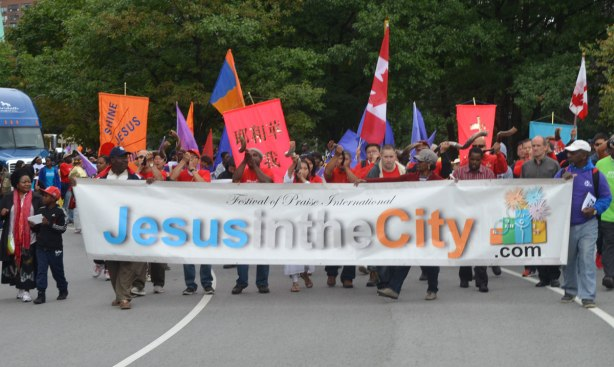 Many people holding a long banner at the start of a parade. The banner says Jesus in the city. This is the name of the parade.