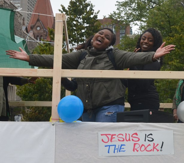 Two young black women on a float in a parade. One has her arms outstretched wide as she sings along with some music. Under them is a sign that says Jesus is the Rock.