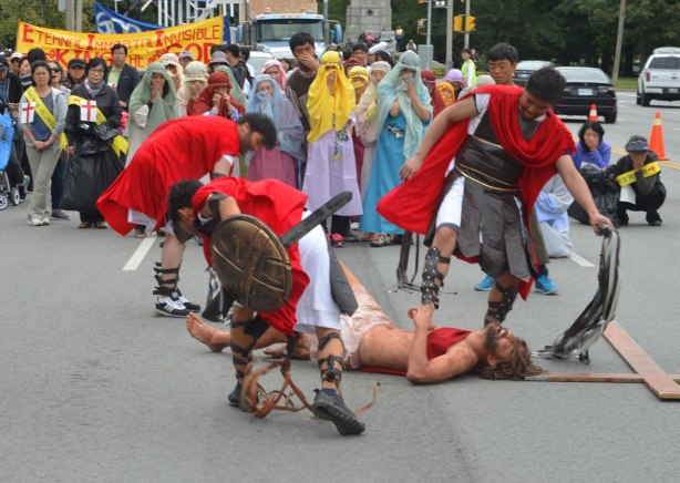 Four men are reenacting Jesus being taken by the Romans for crucifixion. A man is on the ground while the Roman soldiers whip and beat him. A cross is lying on the ground too. A group of upset women onlookers (part of the acting) follow behind. Part of the Jesus in the city parade.