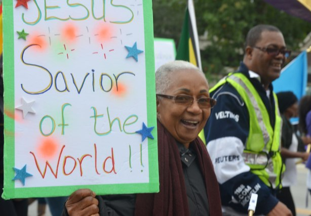 An older black woman with a very big smile is holding a sign that says Jesus is the Savior of the world. She is walking in the Jesus in the City parade in Toronto.