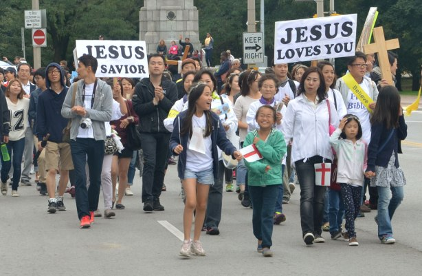 A group of people, mostly young and mostly Asian, are walking in a parade. One is holding a sign that says Jesus loves you. Another person is holding a sign that says Jesus is Savior.