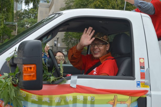 An Asian man driving a truck waves to the camera.