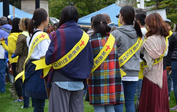 That backs of 4 young women. THey are all wearing sweaters and yellow sashes. The sashes have Korean or maybe Chinese lettering on them as well as a red cross.