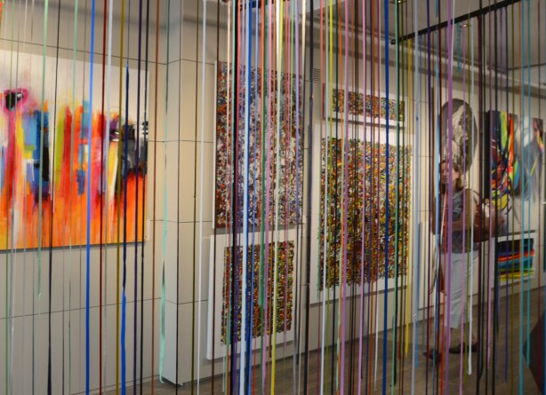 Curtains of long strips of dried acrylic paint in many bright colours hang from the ceiling of an art gallery.