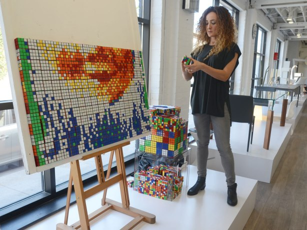 A woman is getting a rubiks cube ready to add to a picture that she is making using 500 rubiks cubes. The picture, about half done, is on an easel in the window of a store.