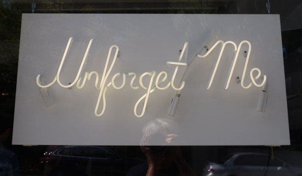 In sursive writing the words Unforget Me in neon tubing to make a sign that is hanging in a store window.
