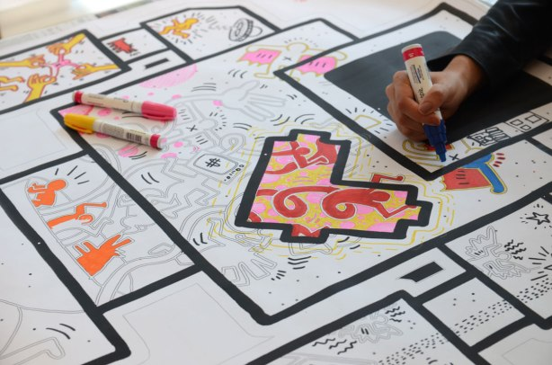 A large lovebot on paper is on a table. Black lines on white paper. It is more than a meter high. There are shapes in the middle and it is designed to be coloured. A hand holding a black sharpie is also in the picture, colouring part of the lovebot