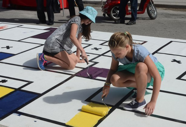 painting a large Mondrian-like painting on the street. A large mat is laid out along Frederick Street and students have marked off squares and rectangles with tape. People are painting the shapes in red, orange, yellow, green and purple.