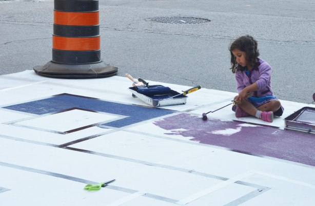 painting a large Mondrian-like painting on the street. A large mat is laid out along Frederick Street and students have marked off squares and rectangles with tape. People are painting the shapes in red, orange, yellow, green and purple. A young girls is using a small roller to paint purple in this picture
