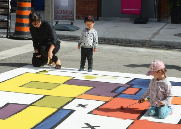 painting a large Mondrian-like painting on the street. A large mat is laid out along Frederick Street and students have marked off squares and rectangles with tape. People are painting the shapes in red, orange, yellow, green and purple. A small boy watches while his mother and a girl paint