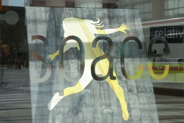 Part of the store window for the store Relative Space. The word space is seen in this picture. In the window is a design of a woman's silhouette in light yellowish woods inlaid into grey flooring.