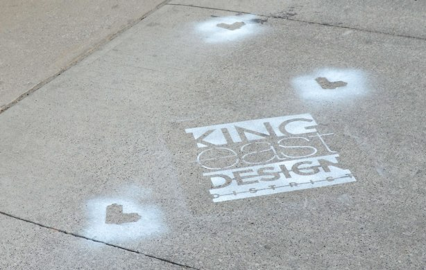 A section of sidewalk. On it is painted the logo for King East Design District. There are also three lovebot stencil shapes spray painted in white on the sidewalk.