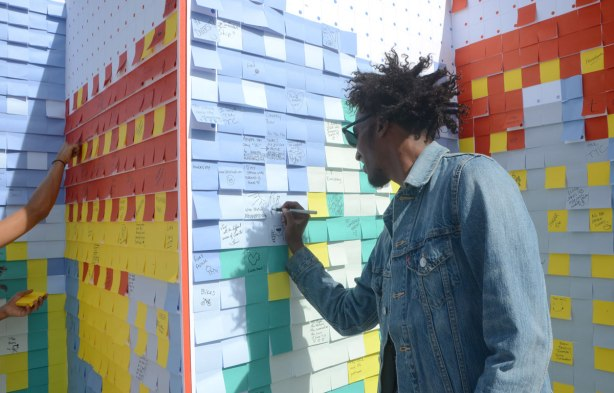 A man with spiky black hair is writing on a board covered with different coloured post it notes.