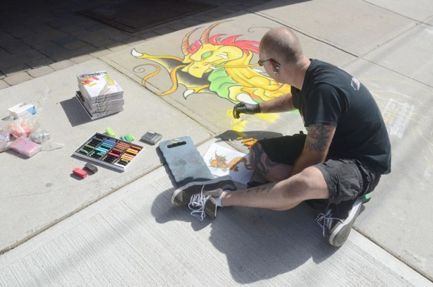 A man is creating a dragon drawing in chalk on a sidewalk.