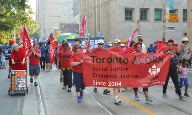 A labour day parade, people in red t-shirts walk behind a red banner for Toronto ACORN, Social Justice, Economic Justice. ACORN stands for Association of Community Organizations for Reform Now.