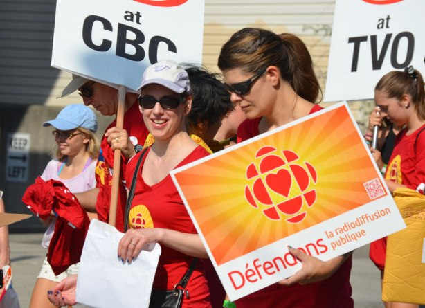 Two women walk in a Labour day parade in support of the CBC