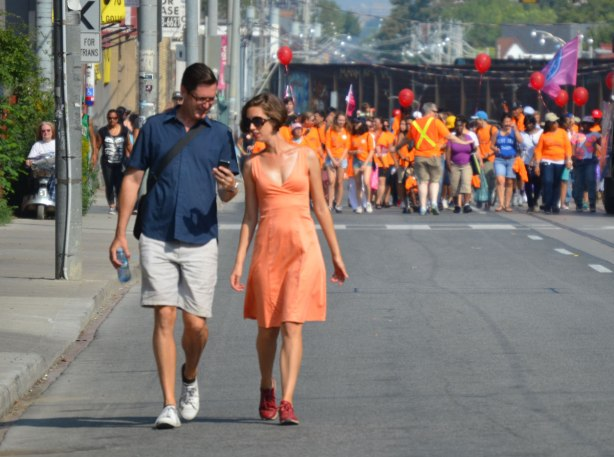 A couple look at his phone while they walk down Dufferin Ave. in front of a parade. Walkers in the parade are in ornage t-shirts in the background.