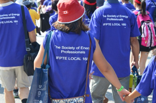 The backs of a group walking in a labour day parade, they are wearing purple t-shirts with the words The Society of Energy Professionals, IFPTE local 160. One of the women is wearing a red hat with a Canadian flag on it.
