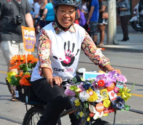 An Asian woman rides her bike in a labour day parade. She is wearing a CUPE 2484 shirt. Her bike has two baskets, one in front and one behind. Both are covered with artificial flowers and buttons. She has a small NDP flag in the back basket.
