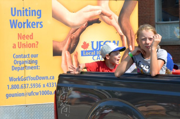 Two kids in the back of a pick up truck in a lbaour day parade. The truck is pulling a trailer with a picture of a circle of hands