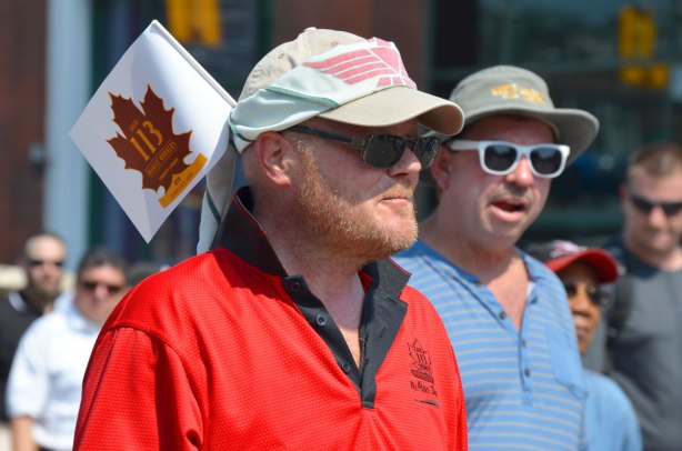Men walking in a labour day parade. They are wearing baseball caps. One of them has a small union flag tucked into the back of his cap. transit workers local 113