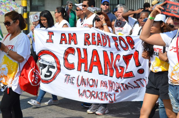 A group walking in a lbaour day parade, they are carrying a large banner that says I am ready for change, the Union of hospitality workers