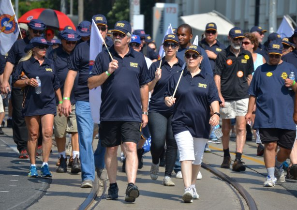 men and women from IBEW (electrical workers) walk in a labour day parade