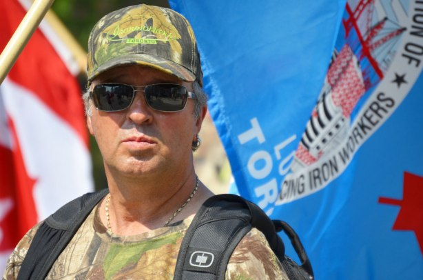 I man from the shoulders up. He is wearing a camo like t-shirt and hat with the ironworkers union label, and he is standing in front of a blue ironworkers flag.