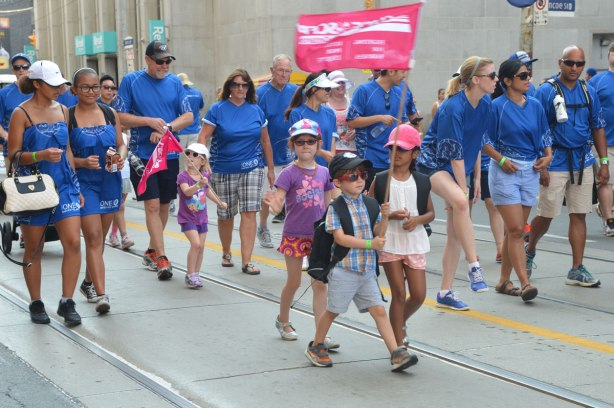 Four kids with flags walking in a labour day parade with their parents.