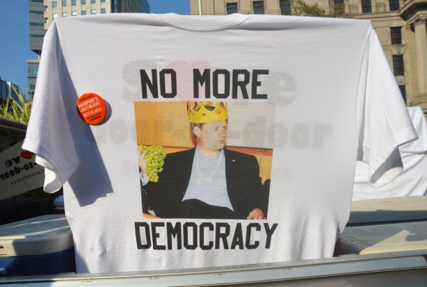 A t-shirt hanging in the window of a car. It has a picture of Stephen Harper wearing a crown and the words No More Democracy. There is a button on the t-shirt that says Harper's last day, 19th October 2015.